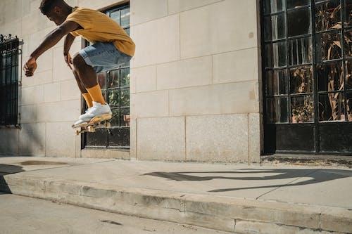 Crop faceless black man jumping on skateboard on street