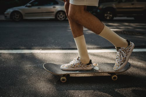 Crop faceless skater riding skateboard on roadside