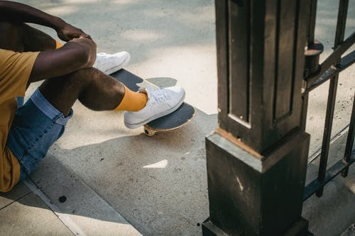 Side view crop anonymous fit African American male skater sitting on roadside with feet on skateboard in daylight