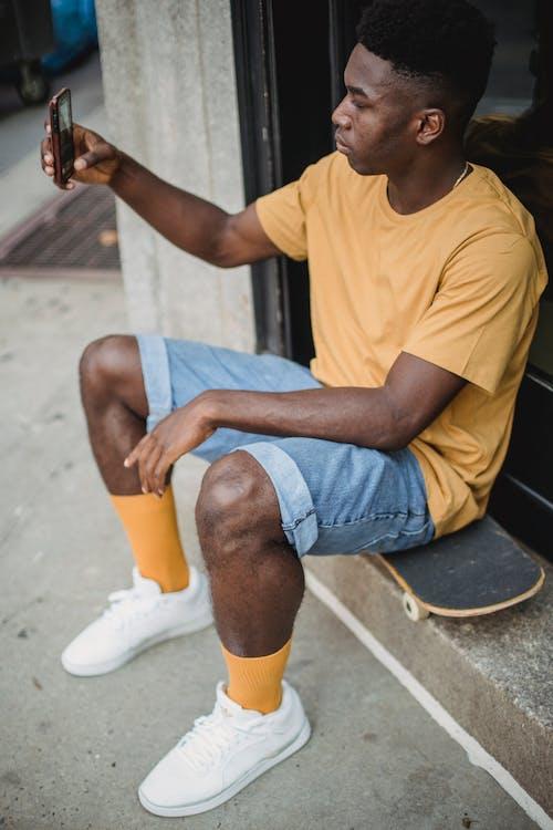 Calm black male skater taking selfie on smartphone on street