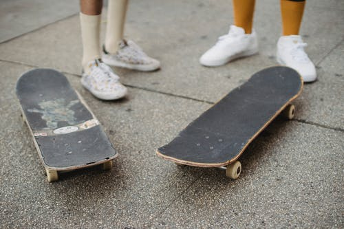 Crop unrecognizable skaters in gumshoes standing near skateboards on city street on summer day