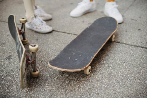 Crop faceless skaters standing on street near skateboards