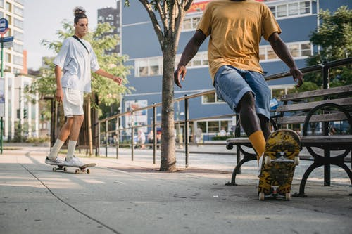 Calm multiracial skaters in casual clothes riding skateboards on walkway on street in city in daytime