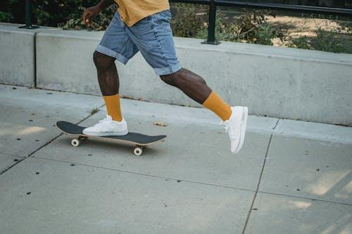 Black man riding skateboard on street