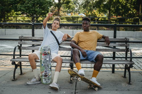 Young men sitting on bench with skateboards in park