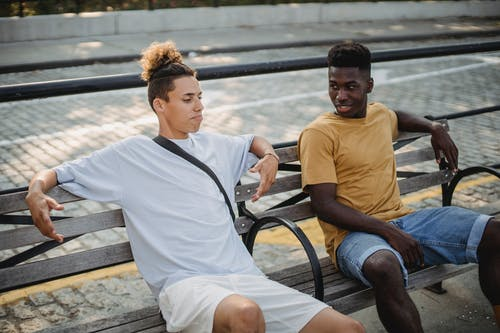 Positive young African american man wearing shorts talking with male friend while spending free time together on wooden bench on urban background