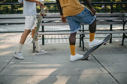 Crop unrecognizable African American guy standing on skateboard while male friend standing behind with board on city street on sunny summer day