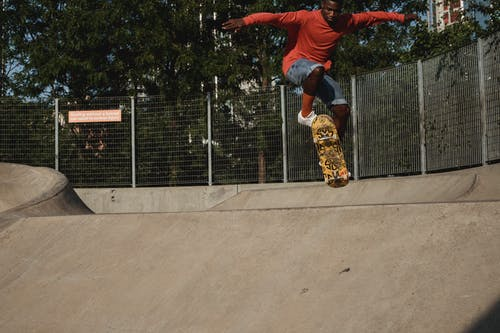 Crop African American male skateboarder performing dangerous ollie stunt on concrete ramp in skate park located in city on sunny day
