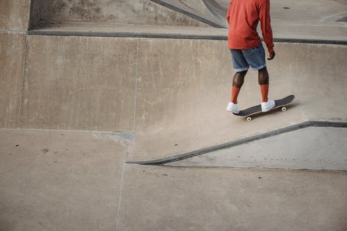 Crop unrecognizable African American skateboarder wearing red long sleeve t shirt and socks with white sneakers practicing stunts during training in skatepark in daytime