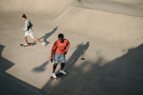From above of man diverse friends accelerating for performing extreme stunt on skateboard during training on modern ramp in skate park