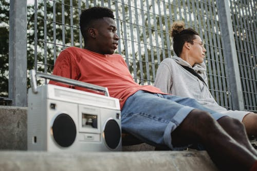 Diverse friends with boombox resting near fence in park