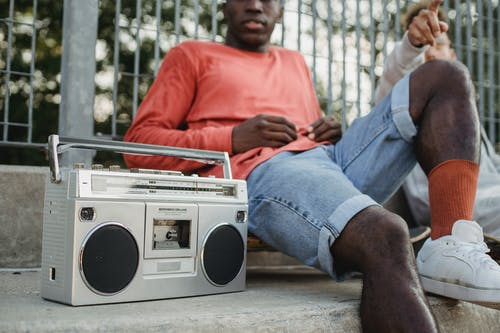 Diverse friends chilling on street with vintage radio cassette recorder