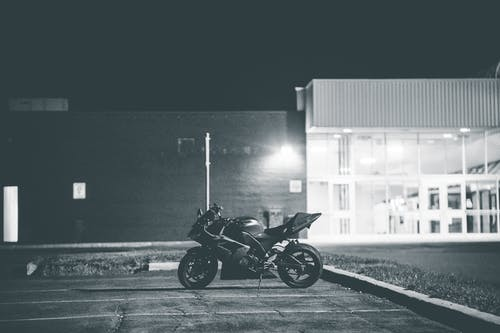 Black and white of stylish motorcycle parked on asphalt surface on local street of city at night