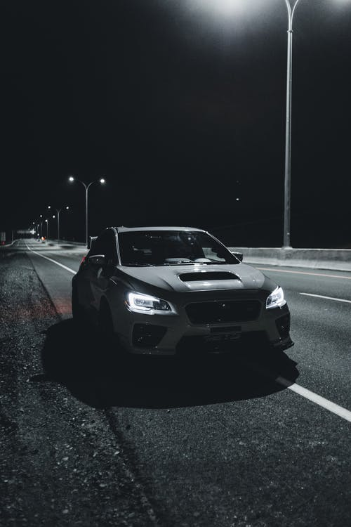 Car with bright headlights driving on highway