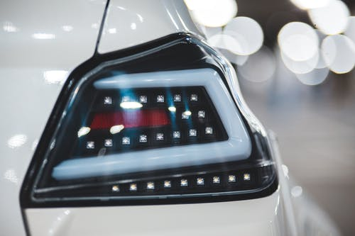Closeup of shiny white colored vehicle with stylish headlight against blurred lights of parking lot
