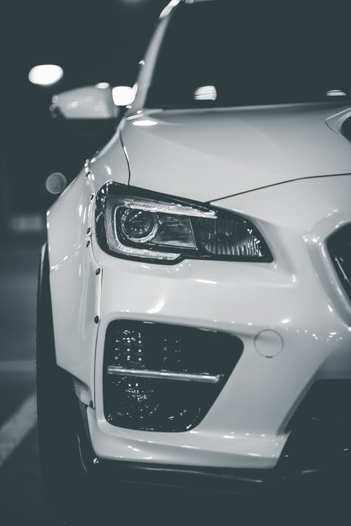 White colored luxury car with shiny headlights and glossy bumper parked at parking lot