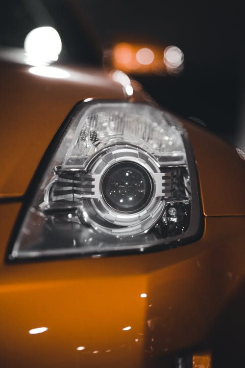 Closeup of shiny glass light at front of motor vehicle against blurred lights of lamp