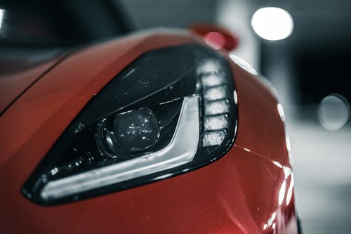 Closeup of elegant shiny headlight of new red expensive sport car parked at car park