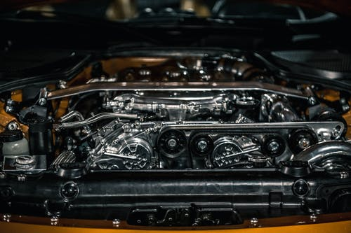 From above of polished stainless engine and automobile apparatuses under hood of new car