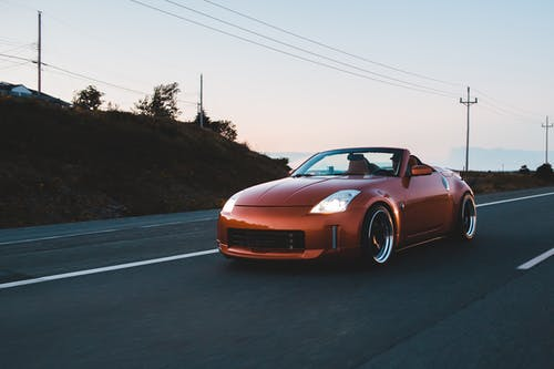 Stylish cabriolet with silver wheels driving on highway
