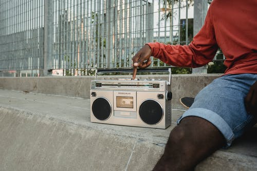Black man pressing button on retro cassette player while sitting outdoors