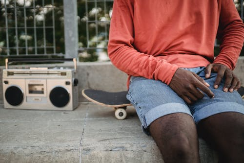 Crop anonymous African American man wearing casual clothes sitting on black skateboard near metal railing and listening to music on vintage cassette recorder
