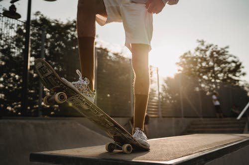 Crop male skateboarder standing on tail of board in sunlight