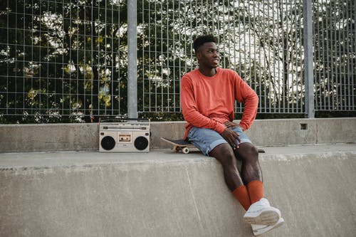 Cheerful young African American male skater sitting on skateboard near metal railing and listening to songs on vintage cassette recorder on sunny day