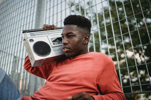 Young pondering African American male listening to radio from old tape recorder while looking forward near grid fence in town