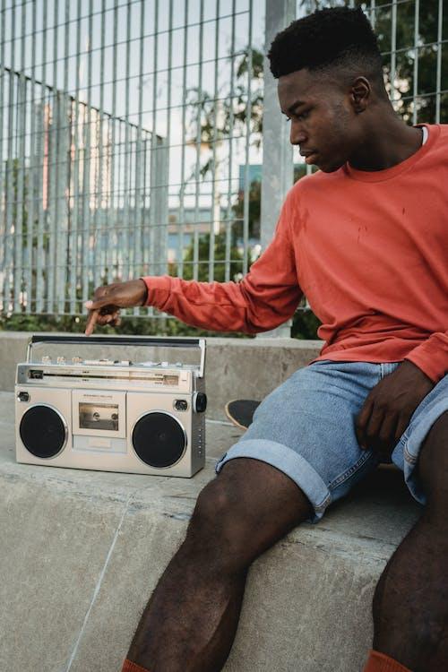 Black skateboarder pressing button on retro tape recorder on street