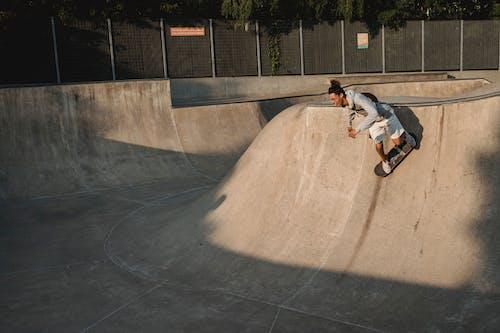 Slim male athlete balancing on skateboard while practicing extreme sport on platform in urban skate park
