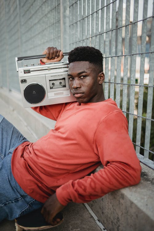 Black skateboarder listening to music on vintage cassette recorder outdoors