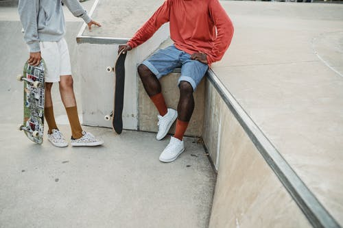 Crop unrecognizable male skateboarders in casual clothes having conversation on ramp in skate park