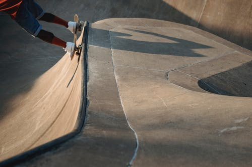 Crop unrecognizable male skater riding skateboard on ramp and performing trick in skate park