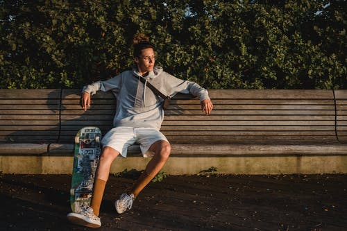 Full body of young male skater sitting on wooden bench in park and thinking