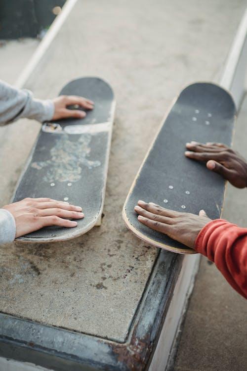 Crop diverse men with skateboards