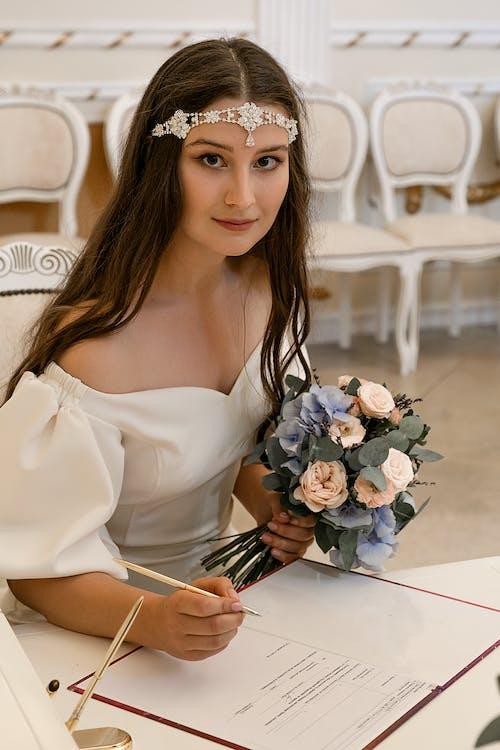 Elegant bride in diadem signing papers in registry office