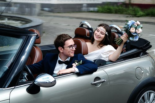 Joyful newlyweds sitting in modern cabriolet