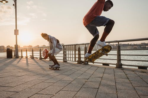 Young energetic diverse male skaters in casual outfits jumping and performing tricks while riding skateboards on embankment