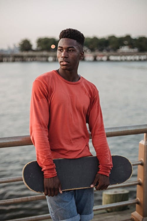 Thoughtful young African American male in casual clothes standing on embankment near fence on embankment and looking away