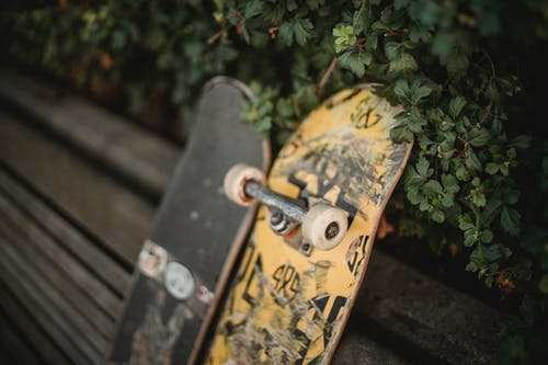 Shabby skateboards with rubber wheels placed on wooden bench in park near green fence