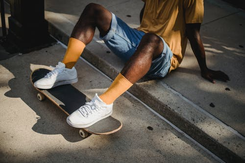 Crop anonymous African American male skater in t shirt and denim shorts sitting on sidewalk with feet on skateboard