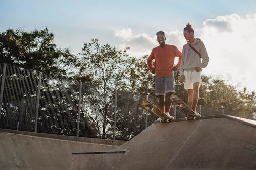 Full body of smiling multiracial male skaters in casual outfits standing on ramp and preparing to ride skateboards