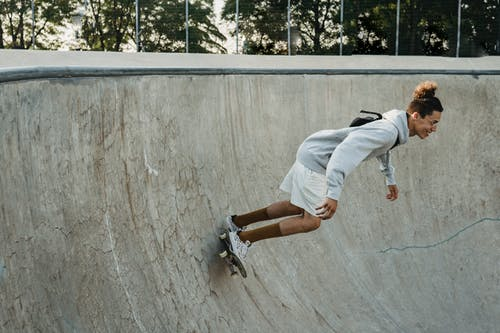 Full body of young male skater in casual outfit and glasses riding skateboard on ramp and performing tricks in skate park