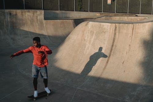 Black skater on ramp in park