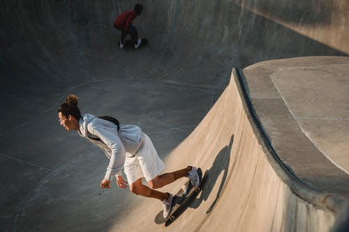 Full body of young male skaters in casual clothes riding skateboards on ramp in skate park