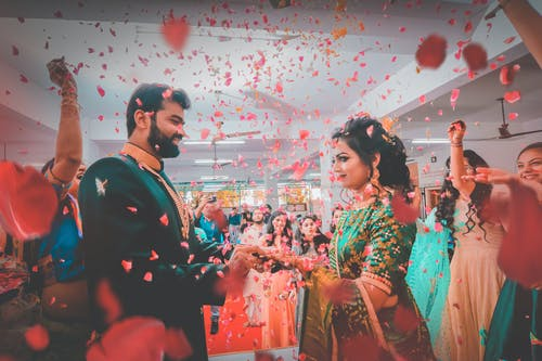 Indian people in bright festive clothes smiling and congratulating newlywed ethnic couple in falling red petals