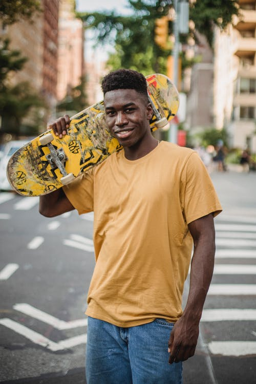 Man in Yellow T-shirt Holding a Skateboard