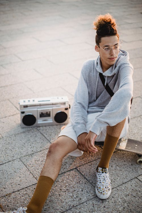 From above of young confident male skater in white shorts and hoodie sitting on skateboard on pavement and listening to music in retro tape recorder