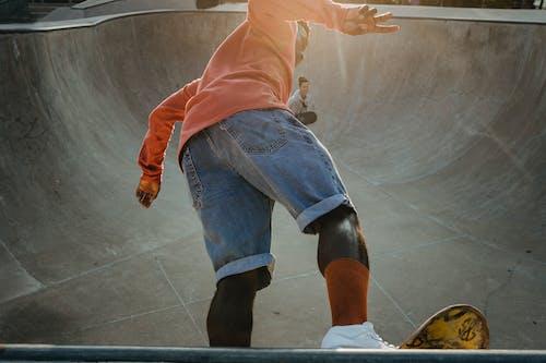 Active black skater performing tricks on ramp in skate park